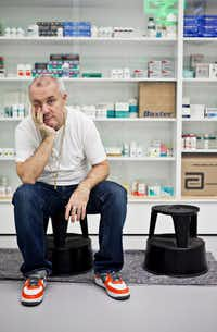 Damien Hirst in 2013 in front of his installation 'Pharmacy'€ (1992) at the Museum of Islamic Art in Doha, Qatar. (Natalie Naccache/The New York Times)