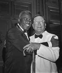 In this July 20, 1962, file photo, baseball player Jackie Robinson embraces Branch Rickey in New York. Rickey was general manager of the Brooklyn Dodgers when Robinson was hired. (The Associated Press)