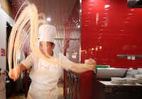 """Zhang Xue """"Charlie"""" Liang hand pulls dough to make noodles at Imperial Cuisine. (Rose Baca/Staff Photographer)"""