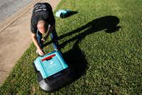 Robin co-founder and CEO Justin Crandall works with a few of the company's Roomba-like lawnmowers.(Smiley N. Poole/Staff Photographer)