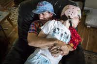 Mark Zartler restrains his daughter to keep her from hitting herself as he rocks with her in a chair after giving her a marijuana vapor treatment on Saturday, March 18, in Richardson. Within minutes, Kara was calm. (Smiley N. Pool/The Dallas Morning News)