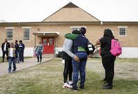 <p>Parent Catrina Henderson (center, in blue shirt), comforts a distraught student at the school's Dallas campus after the closing was announced. (Jim Tuttle/The Dallas Morning News)</p>