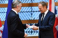 Britain's ambassador to the EU Tim Barrow (L) delivers British Prime Minister Theresa May's formal notice of the UK's intention to leave the bloc under Article 50 of the EU's Lisbon Treaty to European Council President Donald Tusk in Brussels on March 29, 2017.  Britain formally launches the process for leaving the European Union on Wednesday, a historic step that has divided the country and thrown into question the future of the European unity project. (EMMANUEL DUNAND/AFP/Getty Images)