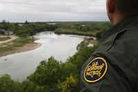 A U.S. Border Patrol agent scans the U.S.-Mexico border from a bluff overlooking the Rio Grande River in Roma, Texas. (John Moore/Getty Images)