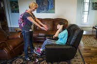 Christy Zartler tries to encourage her daughter Kara to get up to go to the school bus as she rocks herself in her favorite spot, a black leather chair that she rocks back and forth in, before school. (Smiley N. Pool/The Dallas Morning News)
