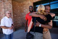 "Exoneree Johnnie Lindsey hugs Dorothy Budd, author of ""Tested: How Twelve Wrongly Imprisoned Men Held Onto Hope,"" alongside fellow exonerees Steven Phillips (far left) and Christopher Scott before a screening of True Conviction that features the three men, at Alamo Drafthouse in Dallas on Friday. (Rose Baca/The Dallas Morning News)"