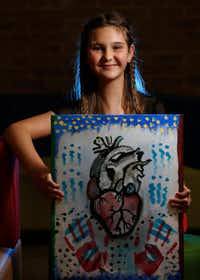 At a follow-up visit to scoliosis surgery, Alexis Brown poses at Texas Scottish Rite Hospital for Children with her painting of a heart.<div><br></div>((Jae S. Lee/Staff Photographer))