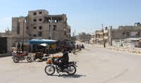 A Syrian man rides his motorcycle in Khan Sheikhun on April 7, 2017 near the area of a suspected chemical weapons attack on their town that killed at least 86 people, among them 30 children, and left hundreds suffering symptoms including convulsions, vomiting or foaming at the mouth. In the Syrian town of Khan Sheikhun, site of an alleged chemical weapons attack on April 4, residents still mourning their dead welcomed US strikes as a way to pressure Damascus. The attack ordered by President Donald Trump was the first direct US military action against Syria's government since the conflict began six years ago.(AFP/Getty Images)