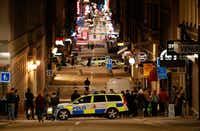 """People stand behind the police cordon as they work at the scene after a truck slammed into a crowd of people outside a busy department store in central Stockholm, causing """"deaths"""" in what the prime minister described as a """"terror attack"""" on April 7. (AFP/Getty Images)"""