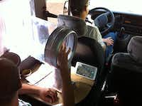 Oxitec workers release thousands genetically modified male Aedes aegypti mosquitoes in Brazil using a GPS locator in a vehicle. (Oxitec)