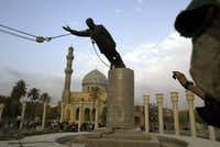A U.S. Marine watches a statue of Saddam Hussein being toppled in Firdaus Square in downtown Baghdad on April 9, 2003 file photo. (AP Photo/Jerome Delay, File)(AP)