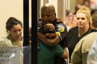<p>A Dallas Area Rapid Transit police officer receives comfort at the&nbsp;Baylor University Medical Center at Dallas&nbsp;emergency room entrance on July 7, 2016. (Ting Shen/The Dallas Morning News)&nbsp;</p>