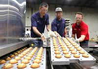 Pablo Arce, left, Josh Garcia, center, and Andrew James take freshly baked blueberry muffins from the Serpentine Auto-Bake oven that can bake 25,000 muffins in an hour at Middleby Bakery Group, a major food equipment company in Plano on Tuesday, April 11, 2017. (David Woo/The Dallas Morning News)(20033462A)