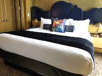 Inside a suite at The Guest House at Graceland in Memphis, a bed features a lightning-bolt-notched headboard against a backlit, glittery gold wall. The tiger pillow is a reference to Elvis Presley's love for karate.