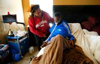 Former NFL player Rickey Dixon gets help sitting up from his wife, Lorraine, as he rests in bed at their home in Red Oak, south of Dallas. (Tom Fox/The Dallas Morning News)