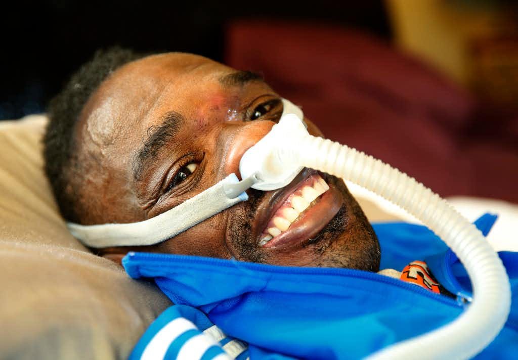 Rickey Dixon, who played for the University of Oklahoma before playing six years in the NFL, cracks a smile as he lays in bed at his home in Red Oak on April 7, 2017. Dixon has ALS and needs help to breathe. (Tom Fox/The Dallas Morning News)