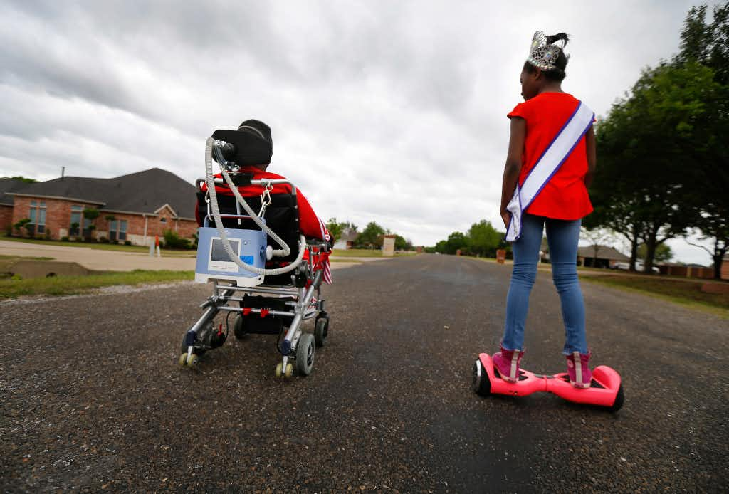 Rickey Dixon, in his wheelchair, and his daughter Alana, who wore a beauty pageant crown and sash while on her hoverboard, ride through their neighborhood in Red Oak on Sunday, April 9, 2017.  (Tom Fox/The Dallas Morning News)