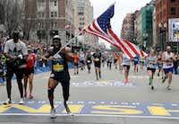 Jose Sanchez, of San Antonio, carries the United States flag across the finish line in the 121st Boston Marathon. (AP Photo/Elise Amendola)AP