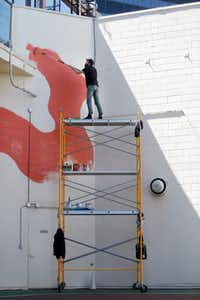 Kyle Steed works on his mural at the Plaza of the Americas.(Rose Baca/Staff Photographer)