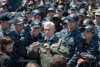 This US Navy handout photo shows US Vice President Michael R. Pence as he poses for a selfie with Sailors on the flight deck of the Navy's forward-deployed aircraft carrier USS Ronald Reagan (CVN 76) on April 19, 2017 at Yokosuka, Japan.  The vice presidents tour of the ship and his remarks to US and Japanese service members highlighted the administrations continuing commitment to rebuilding the US military and to its alliances in the region.(MC2 JAMAL MCNEILL/US NAVY)