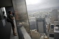 "A woman looks at the Houston skyline from the city's Chase Tower Observation Deck in a photo from 2009. T&L's ranking said plentiful luxury shopping helps ""Houstonians always look their best.""<br>(Houston Chronicle/Michael Paulsen<br>)"