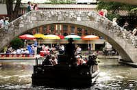 A guided barge trip cruises toward the popular restaurant area along the San Antonio River Walk in downtown San Antonio in a 2007 photo. According to T&L's ranking, city residents ranked perfectly for friendliness. <br>(File photo<br>)