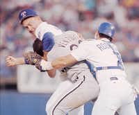 Texas Rangers pitcher Nolan Ryan, left, prepares to defend himself against Chicago White Sox' Robin Ventura, center, during the third inning during a game Aug. 4, 1993, in Arlington. Rangers' Ivan Rodriguez assists Ryan after Ventura charged the mound when he was hit with a pitch.((The Associated Press))