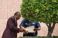 Dallas County Commissioner John Wiley Price steps outside the Earle Cabell Federal Building and Courthouse and signs some paperwork for a man in a Dallas County uniform on Friday. The federal jury deciding the bribery and tax evasion cases against Price will resume deliberations Monday. (Smiley N. Pool/The Dallas Morning News)