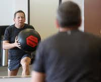 Steven Kincel works out at the overhead ball lunge station at a Core Power class at Corado Fitness.<div><br></div>((Ron Baselice/The Dallas Morning News))