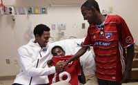 FC Dallas player Atiba Harris, left, visits with 16-yr-old Tamirat Bogale and 16-yr-old Marcos Bogale at Medical Center Plano in Plano, TX, on Dec. 16, 2016. (Jason Janik/Special Contributor)(Jason Janik/Special Contributor)