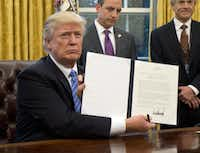 Trump shows the executive order withdrawing the U.S. from the Trans-Pacific Partnership on Jan. 23. He has relied heavily on such presidential directives in lieu of legislative wins. (Ron Sachs/Getty Images)