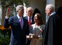 Supreme Court Justice Anthony Kennedy administers the judicial oath to his newest colleague, Justice Neil Gorsuch, in the Rose Garden on April 10, as Gorsuch's wife, Marie Louise, holds a Bible. (Evan Vucci/The Associated Press)