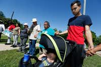 Manuel Perez, next to a stroller holding his son, 1-year-old Sebastian Liam, offered a prayer at the start of the rally on Thursday. ((Nathan Hunsinger/Staff Photographer))