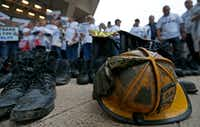 A helmet and the boots of Dallas police and fire retirees lay on the ground at a rally at Dallas City Hall on April 26 supporting a state bill that would bail out the fast-failing Dallas Police and Fire Pension System. (Jae S. Lee/The Dallas Morning News)