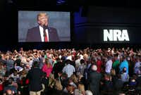 Thousands of NRA attendees watch the keynote by President Donald J. Trump on one of the giant screens in Hall A at the NRA-ILA Leadership Forum on Friday, April 28, 2017, in Atlanta. (Curtis Compton/TNS)