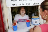 Owner Lee Albert serves Connie Garcia of Dallas as last year's snow-cone season got underway. Albert and husband Ed Schwartz announced Saturday that they will not open for the 2017 season.<br>(Andy Jacobsohn/Staff Photographer)