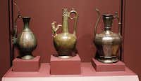 Left to right, Asia: Mesopotamia, Ewer, late 7th or early 8th century made of brass, Syria, Ewer, late 7th or early 8th century made of bronze, and The Homberg Ewer, 1242, from Syria, made with brass with and inlaid with silver, are part of the Spirit and Matter, Masterpieces from the Keir Collection of Islamic Art at the Dallas Museum of Art. The exhibition presents a selection of over 50 masterworks in various mediums and explores 13 centuries of Islamic art making across three continents, from Spain to Central Asia.(David Woo/Staff Photographer)