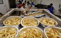 Nancy Rodriguez (center) places cinnamon rolls in a pan at RoRo's Baking Company in Dallas.(David Woo/Staff Photographer)