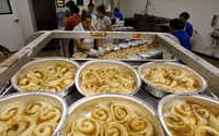 Nancy Rodriguez (center) places cinnamon rolls in a pan at RoRo's Baking Company in Dallas. (David Woo/Staff Photographer)
