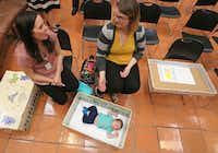 New mothers Rachel Salinas (left) and Taylor Freed visit as 6-week-old Mason Salinas relaxes in a baby box after a news conference announcing the partnering of the Baby Box Co. with Dallas Medical Center at the Farmers Branch facility on Wednesday. (Louis DeLuca/Staff Photographer)