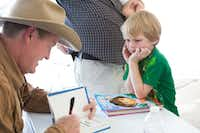 Craig Johnson autographs a book for Eliot Donmoyer, 5, of Austin at the Texas Book Festival in Austin in 2014.(Julia Robinson/Special Contributor)