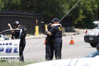 <p>William Bruce (right) embraces son Chase near the scene of Monday's fatal shooting that left two dead and sent paramedic William An to the hospital in critical condition. (Jae S. Lee/The Dallas Morning News)</p>