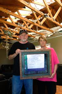 Rickey and Gina Dodson stand inside their home in Emory, Texas holding a photograph of a granite stone on May 2. It was taken at the Palestine, Texas courthouse that bears Gina's maiden and married last names. This photograph survived tornadoes on April 29. (David Woo/Staff Photographer)