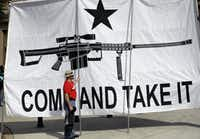 """In this 2015 file photo, a demonstrator helps hold a large """"Come and Take It"""" banner at a rally in support of open carry gun laws at the Capitol in Austin.(Eric Gay/AP)"""