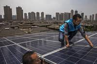 Chinese workers from Wuhan Guangsheng Photovoltaic Company install solar panels on the roof of a building. To ease the country's longtime dependence on coal and other fossil fuels, China's government has made strategic investments in the solar panel industry, which has created intense global competition in the estimated $100 billion global solar energy market.(Kevin Frayer/Getty Images)