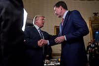 U.S. President Donald Trump meet with James Comey during an Inaugural Law Enforcement Officers and First Responders Reception in the White House in January. (Andrew Harrer/TNS)