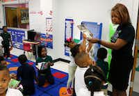Jisel Johnson (center), 4, holding a book, tries to get the attention of Principal Onjaleke Brown at N.W. Harllee Early Childhood Center in Dallas.(David Woo/Staff Photographer)