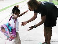 Principal Onjaleke Brown greets student Skylar Thompson as she arrives at Harllee Early Childhood Center in Oak Cliff.(David Woo/Staff Photographer)