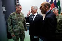 U.S. Defense Secretary James Mattis (center) chats with U.S. Army Gen. John Nicholson (left), commander of U.S. Forces Afghanistan, after a news conference at Resolute Support headquarters in Kabul last month. Mattis arrived unannounced in Afghanistan to assess America's longest war as the Trump administration weighs sending more U.S. troops. (File Photo/The Associated Press)
