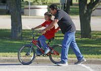 Jose Crispin helps his son, Andrew Garcia, 6, learn to ride his bike at Balch Springs Irwin Park, where vigils were held for 15-year-old  Jordan Edwards, who was shot nearby by a Balch Springs police officer.(Ron Baselice/Staff Photographer)